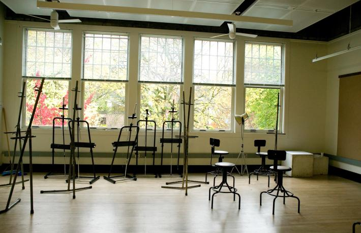 Empty class studio with metal easels and chairs scattered in the room while the room is illuminated by the sunlight from the windows behind them.