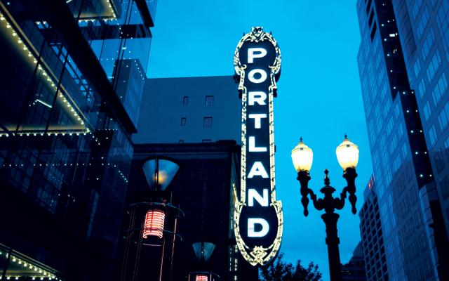 The word 'Portland' displayed vertically on a building sign at night.