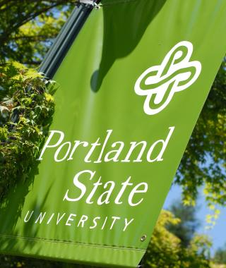 A green hanging banner displaying the PSU logo. The banner is under the sun and surrounded by green trees.