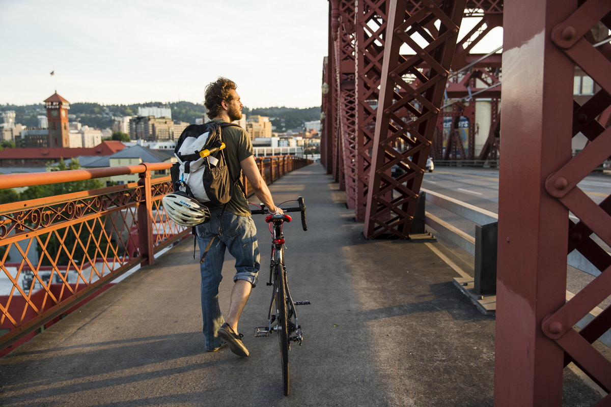 Person with bike walking across bridge
