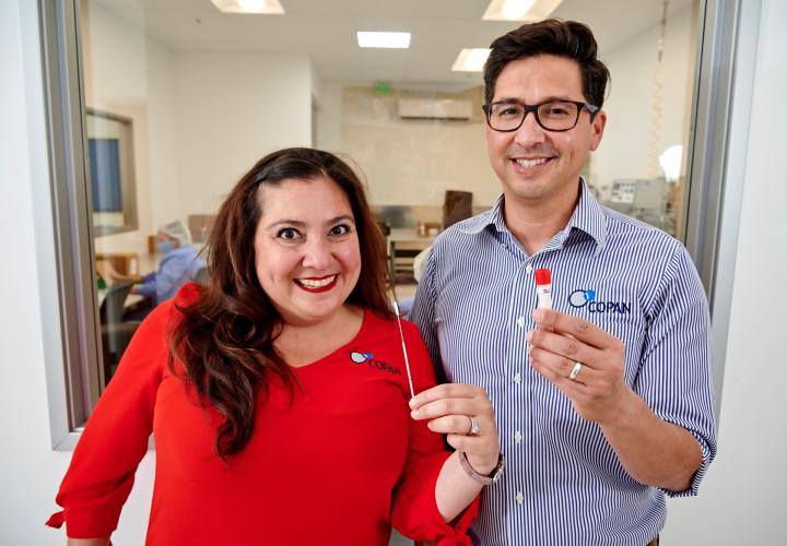 Gabriela and Franco holding up a COVID-19 testing swab kit