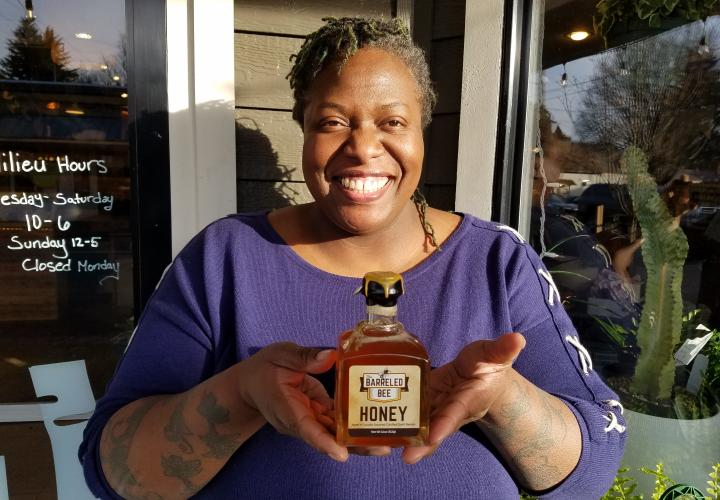 alumna Lee Hedgmon holding her barrel-aged honey bottle