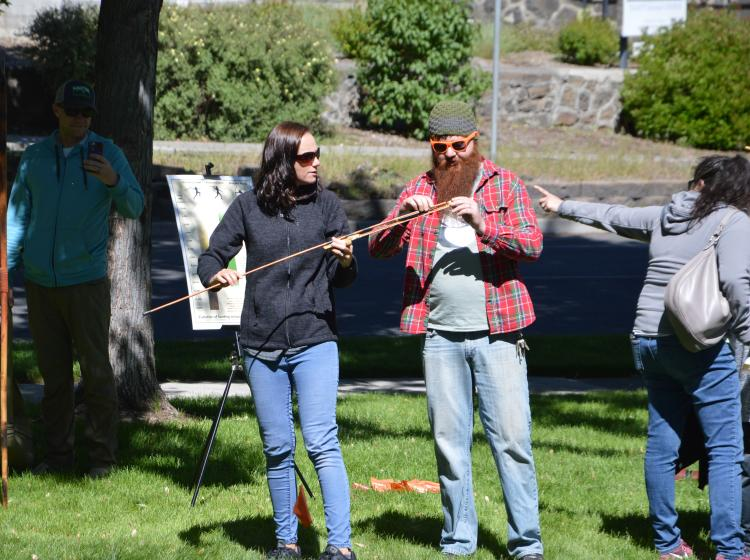 Bend Oregon Archaeology Roadshow volunteer explains how to use the atlatl spear thrower to a visitor at the 2019 event; photo by Beverly Clement