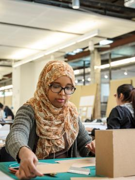 Female student wearing headscarf works with cardboard model at her desk in studio