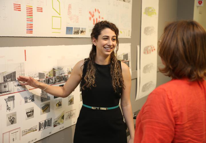 An architecture student discusses her 2D thesis work with her professor