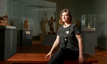 Woman sits in front of sculptures
