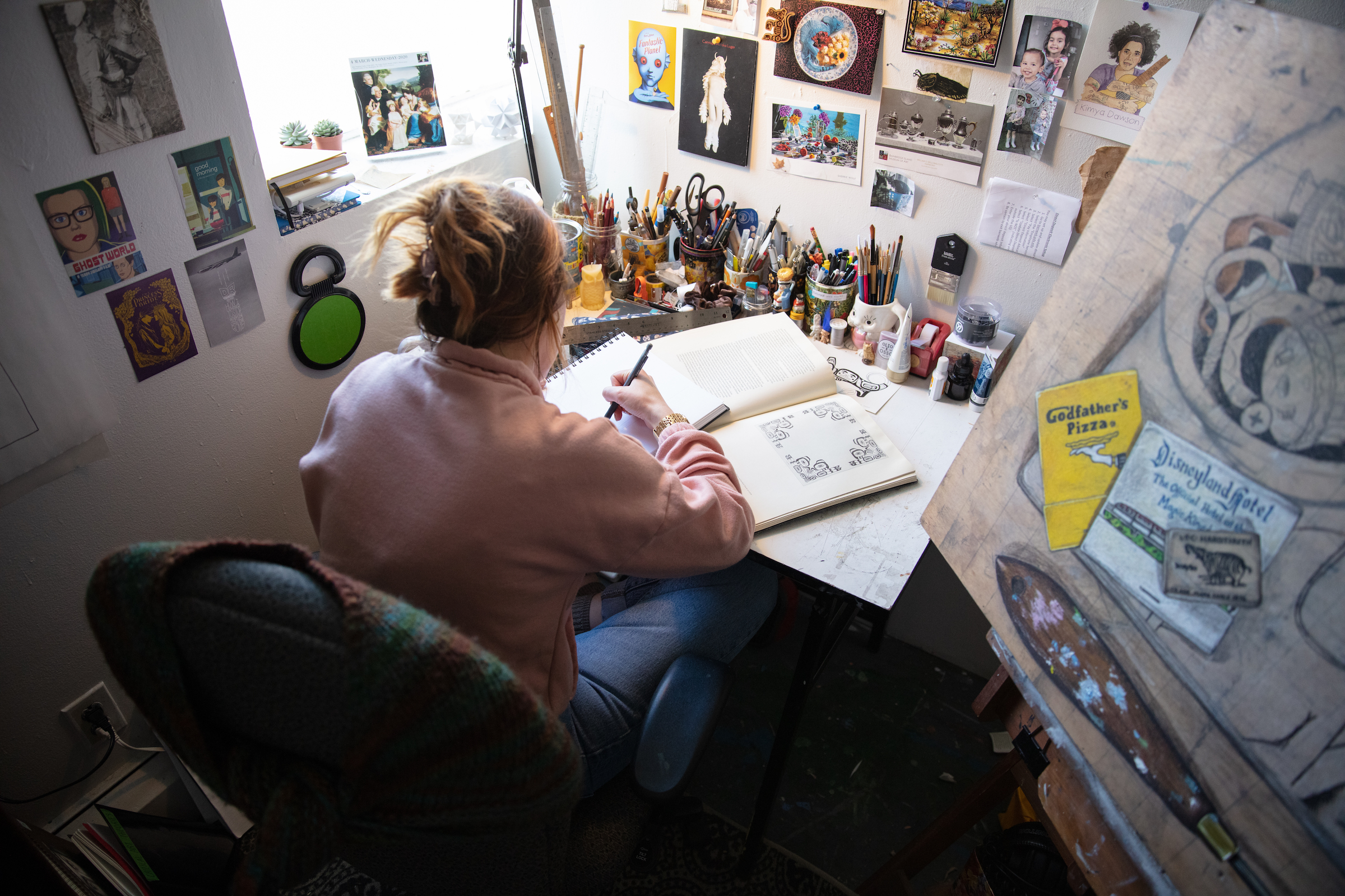 Graduate student working at a drawing table by a window, surrounded by reference images and art supplies