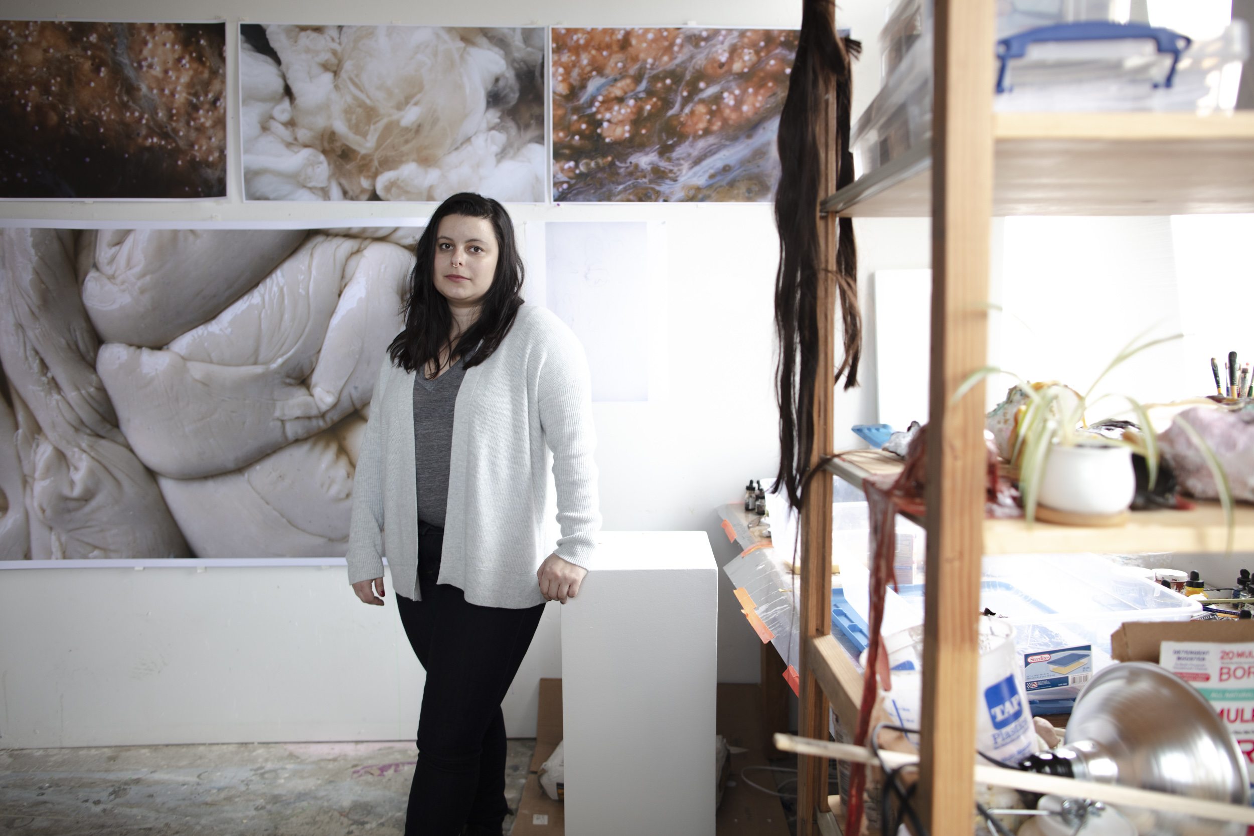 Graduate student Samantha Ollstein standing in her studio surrounded by her artwork