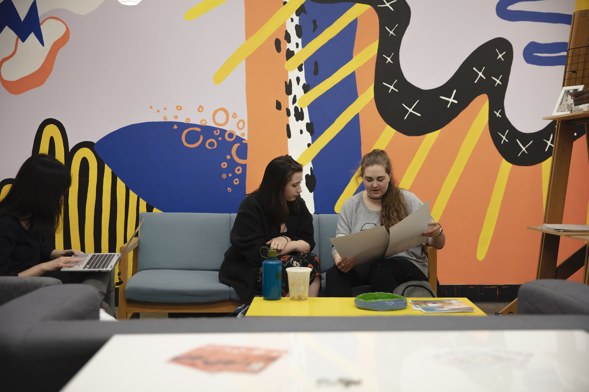 Two women studying on a sofa in front of a colorful mural.