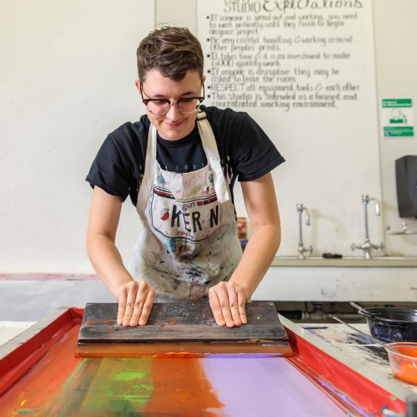 Student drawing colorful ink across a silk screen with a squeegee