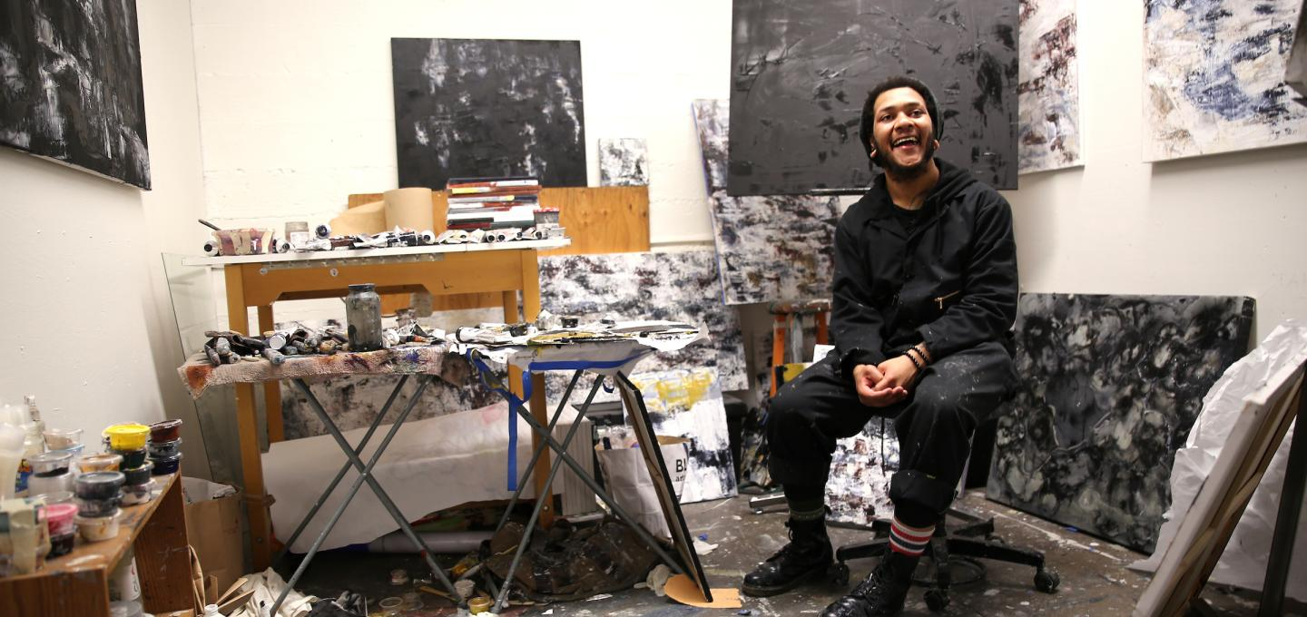 BFA student in studio surrounded by paintings