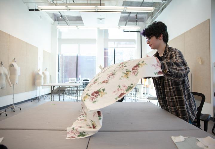 Student unfurling fabric onto a cutting table in the textiles studio