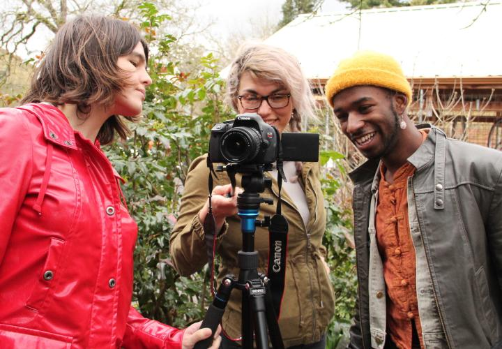 Three students in a video and community course gather around a camera on a tripod
