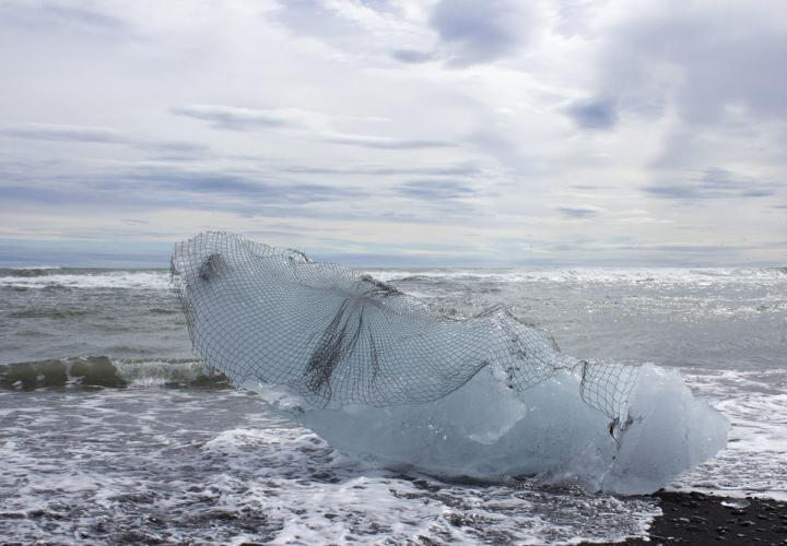 Large chunk of ice on a beach draped in a textile artwork net by Sarah Nance