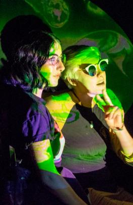 Two students illuminated by a colorful video projection