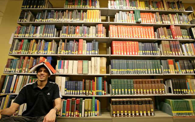 Young man balances an open book on his head while seated in front of a large library bookshelf