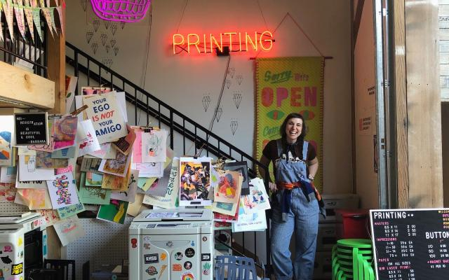 "Kate Bingaman Burt stands next to a Risograph printer under a neon sign that says ""Printing"""