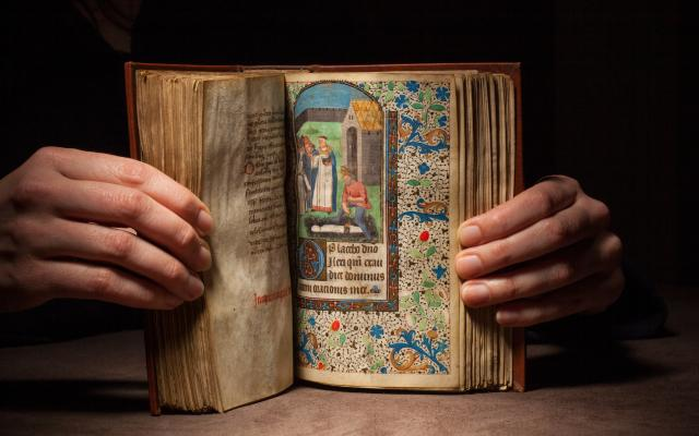 Hands holding open a medieval book of your to a page with illustration of a burial.