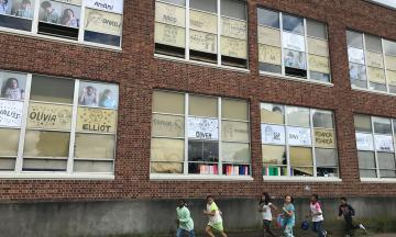 Brick wall of Martin Luther King School with windows covered in student art and five children running in a line at the base of the wall.