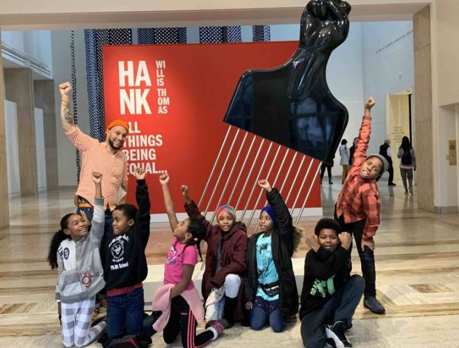 Stevenson and a group of King School students pose with fists raised in front of a sculpture by Hank Willis Thomas at the Portland Art Museum.