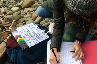 A student writing in a notebook at a rocky beach