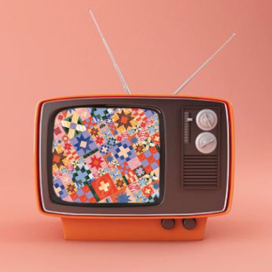 Old style orange television with knobs and silver antennae, a colorful quilt pattern is on the screen.