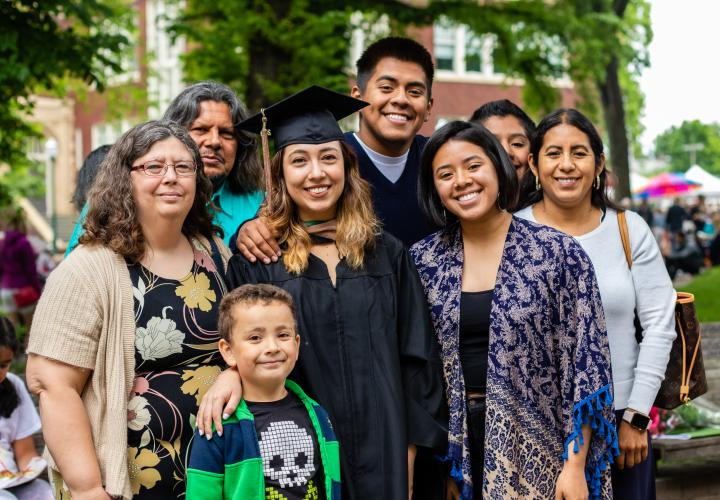 Graduate student posing for picture with multi-generational family members