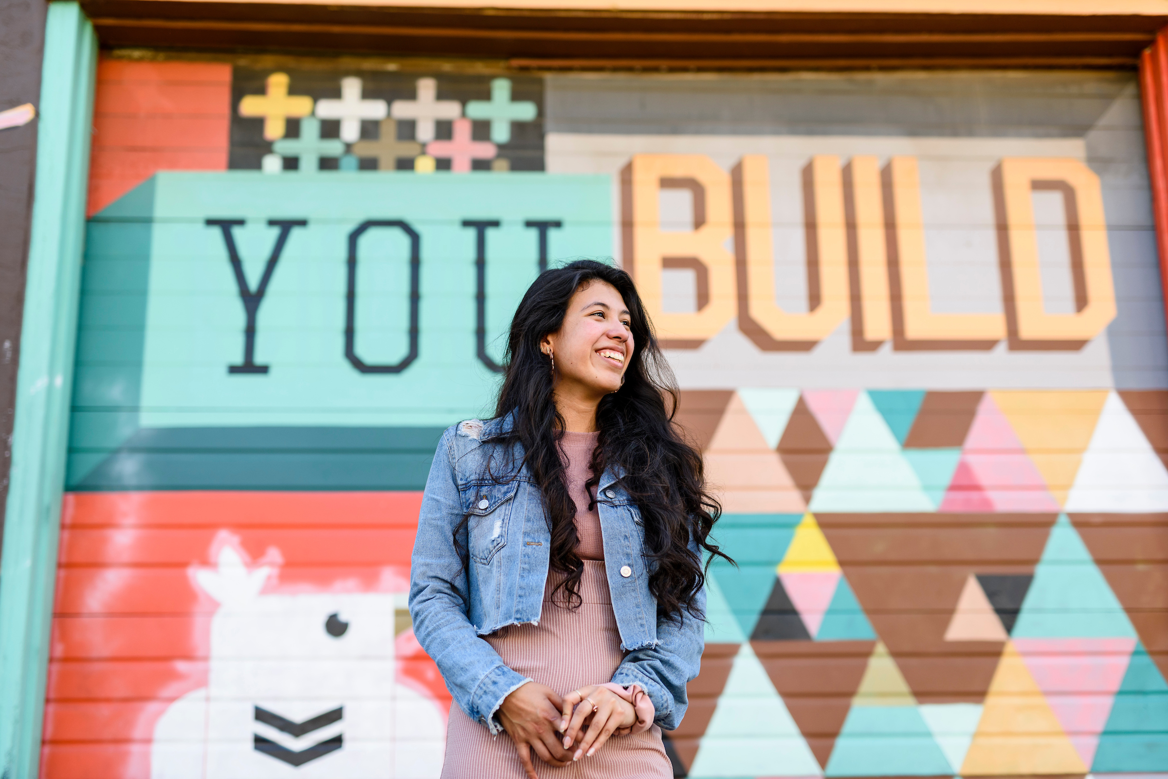 "Student standing in front a mural that says ""You Build"""