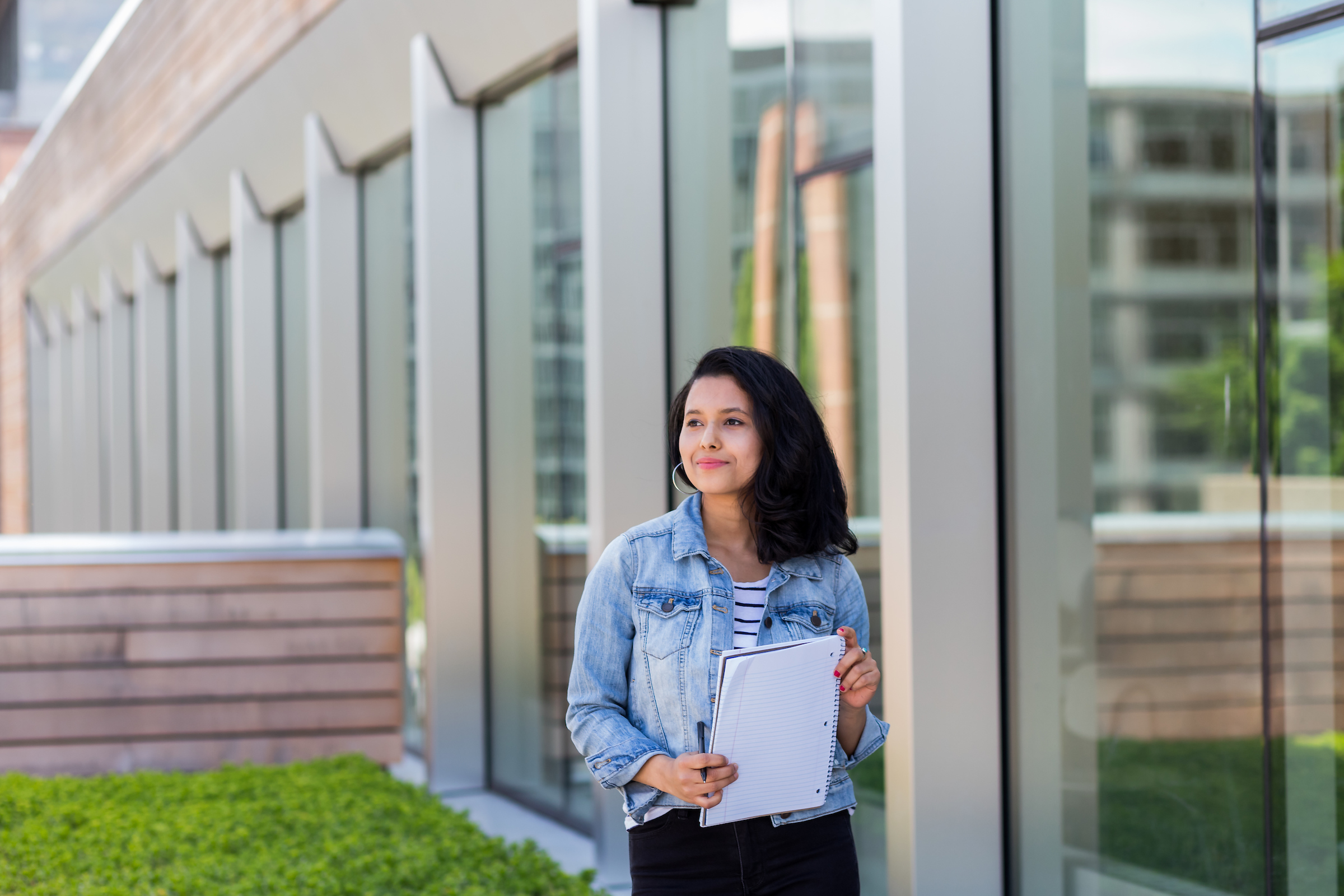 student standing in front of business school
