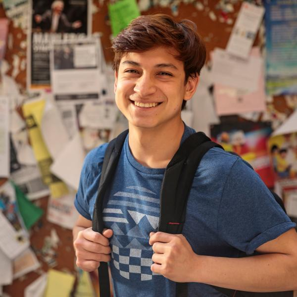 student smiling in front of bulletin board