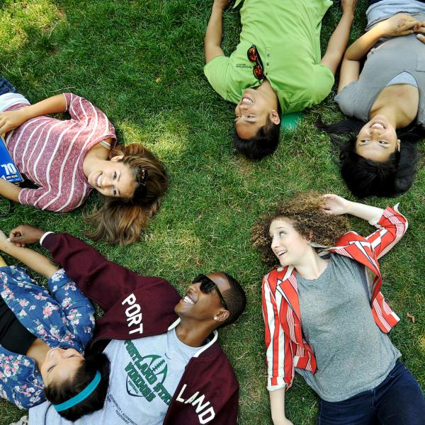 multiple students relaxing in the grass on the park blocks