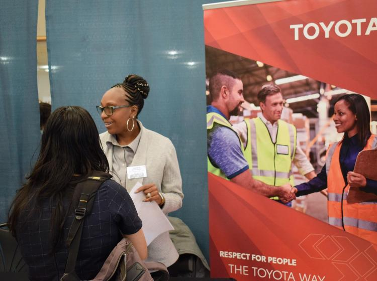 Recruiter from Toyota talking with 3 students