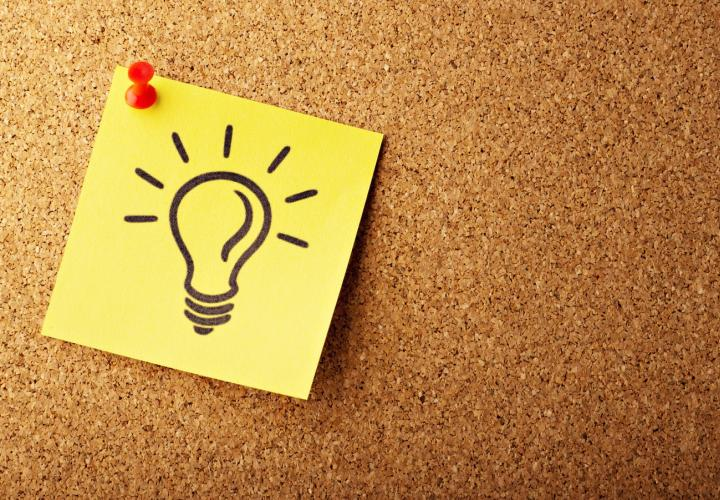 a yellow sticky note with a drawing of a light bulb tacked onto a bulletin board