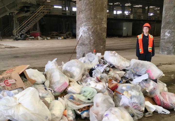 woman standing next to a pile of trash that was picked up