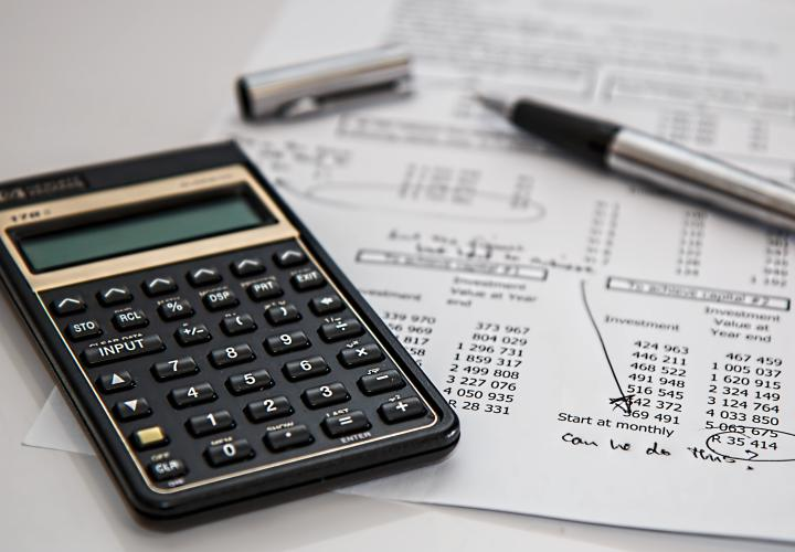calculator and a pen laying on top of finance documents
