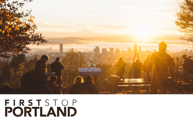 group of people standing around looking out towards the Portland skyline during a sunrise