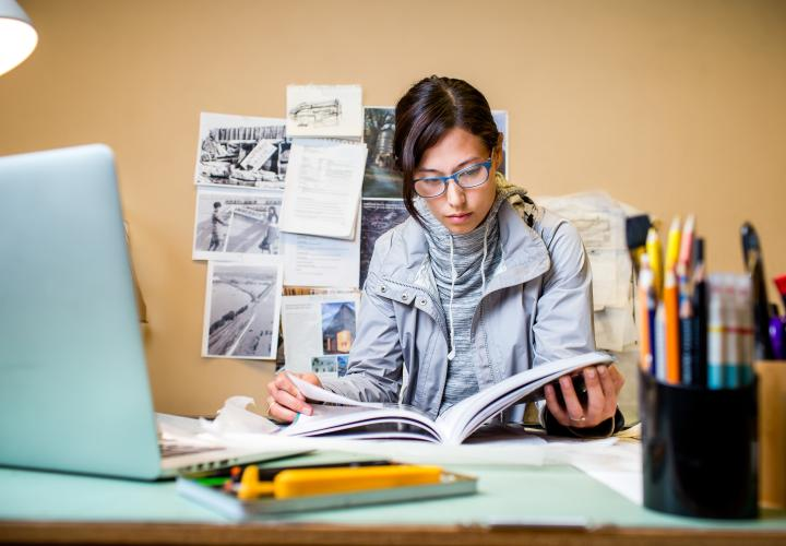 Student studying at desk from a textbook