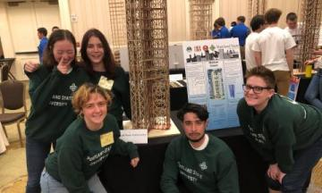 students in the EERI group at a competition, smiling around their balsa wood structure