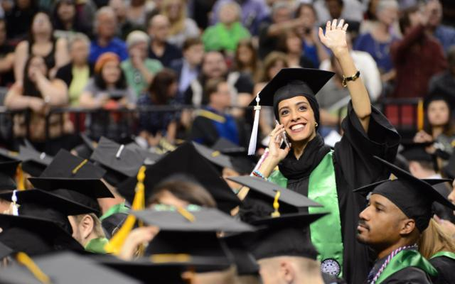 Student waiving to family at commencement