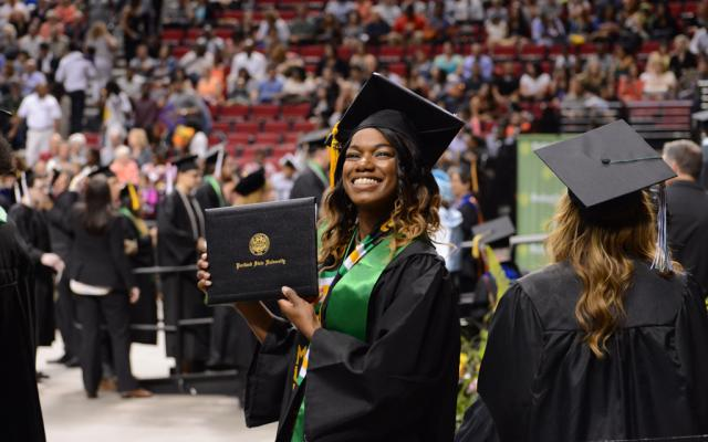 Student showing her diploma at commencement