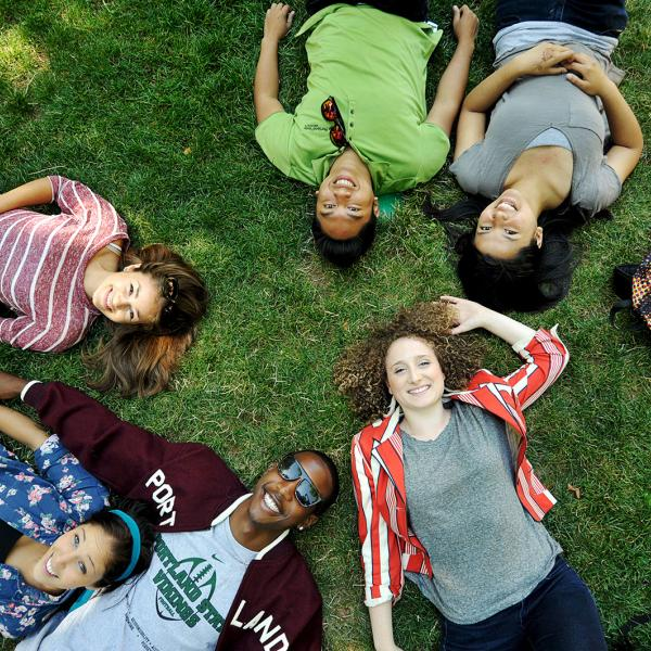 Students lying in grass looking up at camera