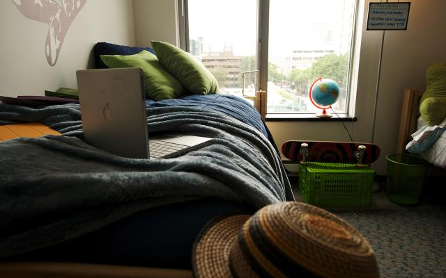 Residence hall room with laptop on bed