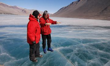 Two researchers stand on an iced-over body of water