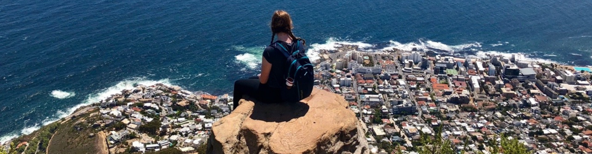 Student peched on Lions Head overlooking Table Bay in S. Africa