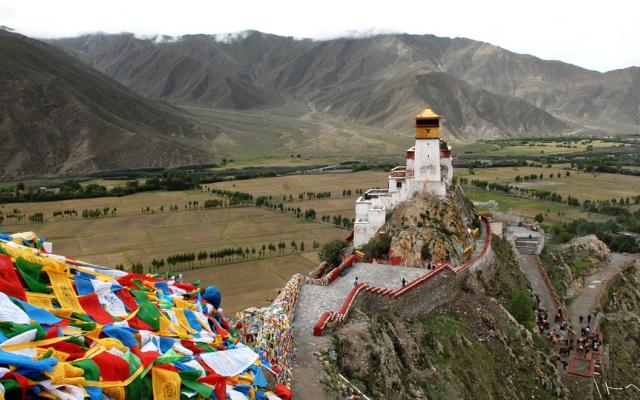 View of Tibetan peace flags and monastery in the mountains.