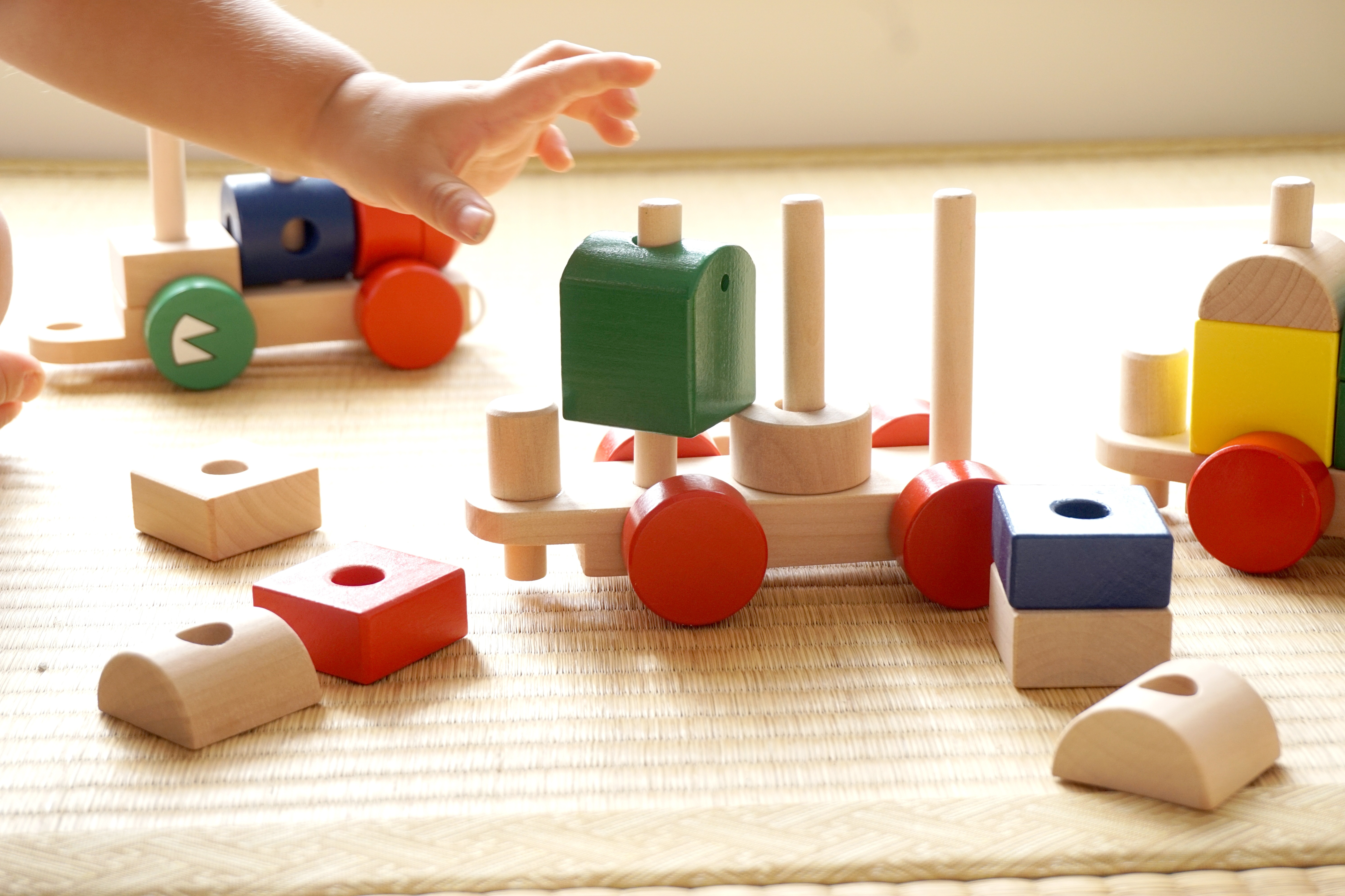 A child's hand reaches for a bright green wooden block surrounded by a colorful wooden train set.