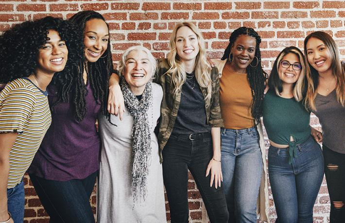 Diverse women beaming with their arms looped around each other