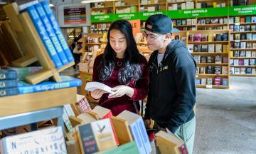 Two people read the back cover of a book at the Portland State University bookstore.