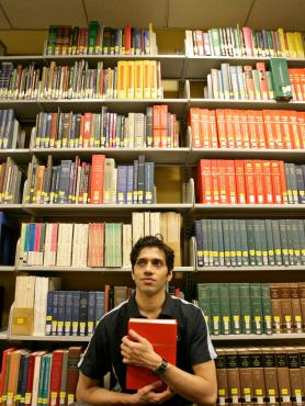 Person holding book sitting in front of stack of books