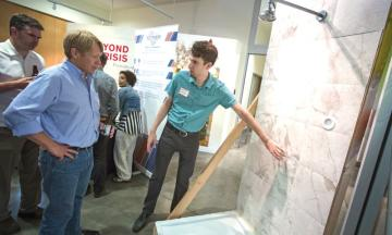 Photo Credit: PAMPLIN MEDIA GROUP: JONATHAN HOUSE - Sam Weiss explains the Portland Shower invention to Calvin Rasmussen during a PDX Tech Meet Up at Mercy Corps. The shower can recycle water, reducing water and heating bills.